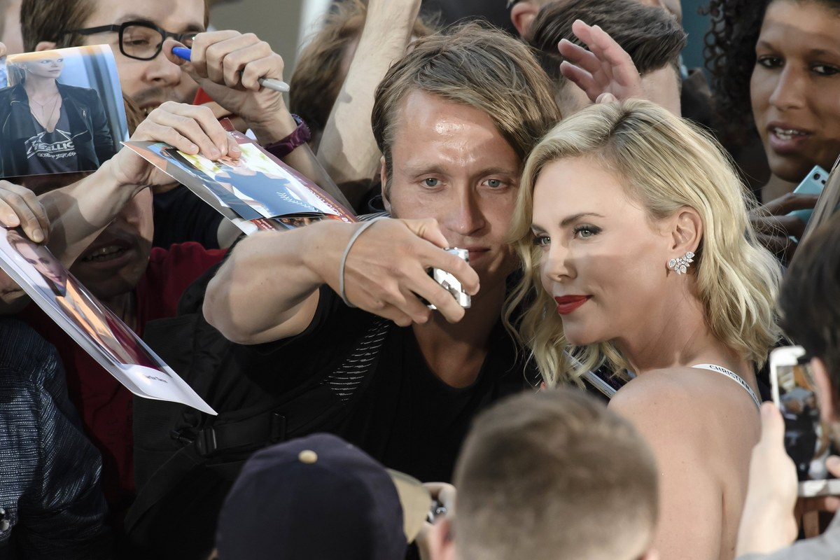epa06093332 South African actress and cast member Charlize Theron (R) takes selfies with fans during the film premiere of 'Atomic Blonde' at the Theater am Potsdamer Platz in Berlin, Germany, 17 July 2017. The movie opens across German theaters on 24 August. EPA/CLEMENS BILAN