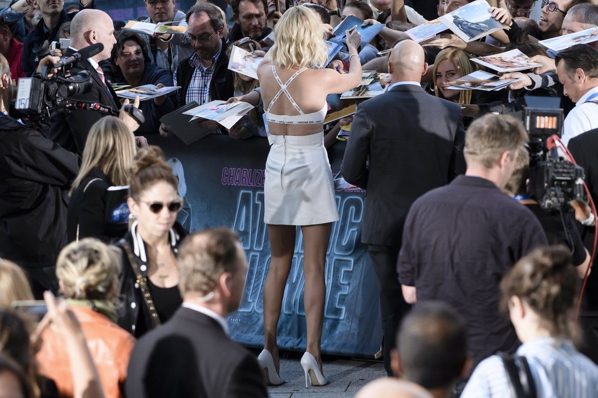 epa06093461 South African actress and cast member Charlize Theron (C) signs autographs during the film premiere of 'Atomic Blonde' at the Theater am Potsdamer Platz in Berlin, Germany, 17 July 2017. The movie opens across German theaters on 24 August. EPA/CLEMENS BILAN