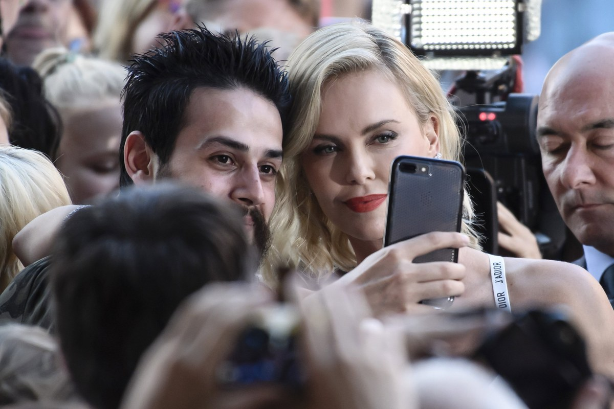 epa06093339 South African actress and cast member Charlize Theron (R) takes selfies with fans during the film premiere of 'Atomic Blonde' at the Theater am Potsdamer Platz in Berlin, Germany, 17 July 2017. The movie opens across German theaters on 24 August. EPA/CLEMENS BILAN